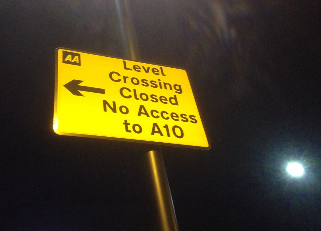 A road sign warns of the closure of the road and pedestrian railway level crossing at Lincoln Road in Enfield, north London. (© London Intelligence)